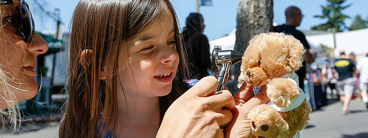 An adult holding a otoscope and a child with a teddy bear.
