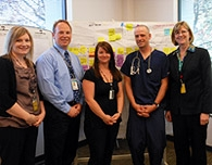 Staff members in front of their Lean project board