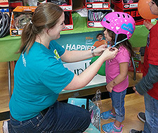 Kaiser Permanente volunteer fits bike helmet on girl