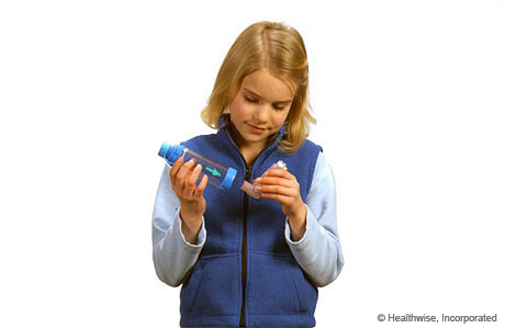 A child putting the inhaler mouthpiece into the spacer