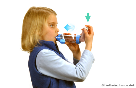 A child pressing down on the inhaler and breathing in